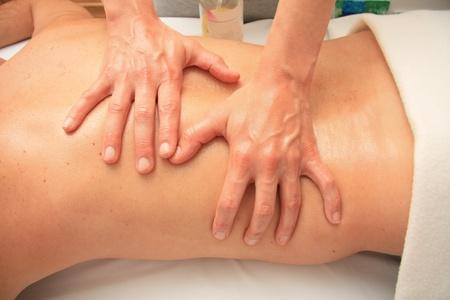 A női masszőr ad egy hátmasszázs