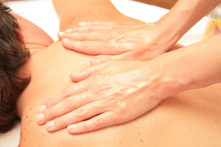 A female masseur giving a back and shoulders massage
