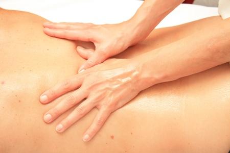 masaje corporal: Un masajista femenina dando un masaje en la espalda