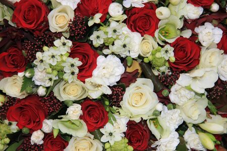 Mixed floral arrangement with red and white roses and lilies photo
