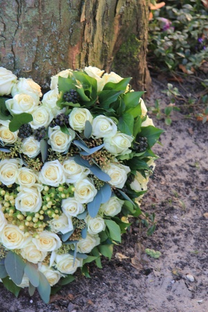arrangement: Heart shaped sympathy flower arrangement with white roses near a tree Stock Photo