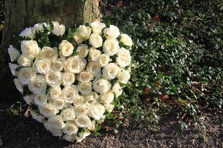 Heart shaped Sympathie Gesteck mit weißen Rosen in der Nähe eines Baumes Lizenzfreie Bilder