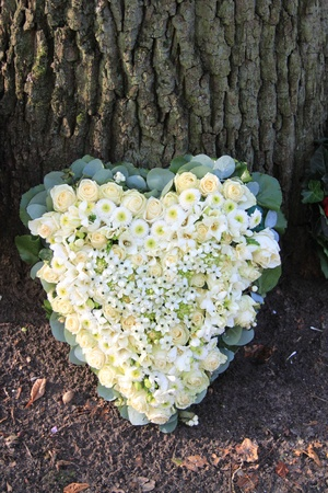Heart shaped sympathy flower arrangement with white flowers photo