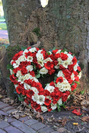 Heart shaped sympathy flower arrangement with red and white flowers