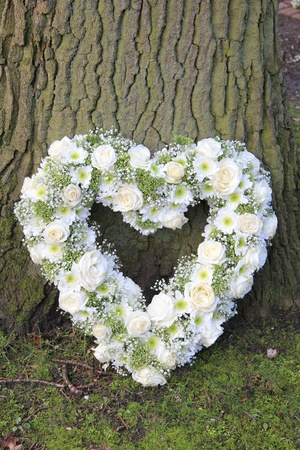 White heart shaped sympathy floral arrangement near a tree
