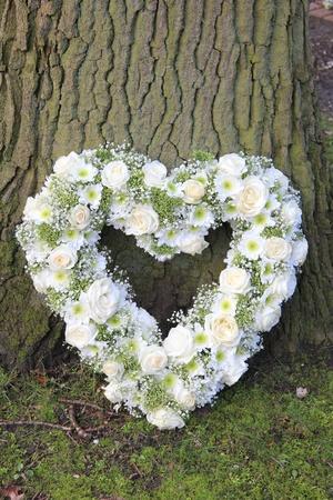 sympathy flowers: White heart shaped sympathy floral arrangement near a tree