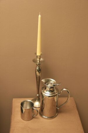 luxery: Living room accessories in silver: candlestickholder, coffeepot and mug combined in a still life