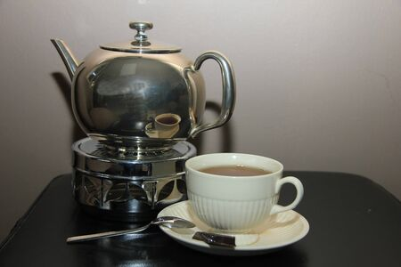 A classic silver teapot and cup in a still life photo