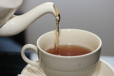 Pouring tea in classic white teacup, close up
