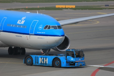 March, 24th, Amsterdam Schiphol Airport the Netherlands: a plane is being pushed back by a tug to avoid jet blast Stock Photo - 12848377