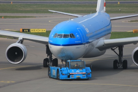 March, 24th, Amsterdam Schiphol Airport the Netherlands: a plane is being pushed back by a tug to avoid jet blast Stock Photo - 12848381