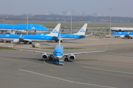 pushed: March, 24th, Amsterdam Schiphol Airport the Netherlands: a plane is being pushed back by a tug to avoid jet blast Editorial