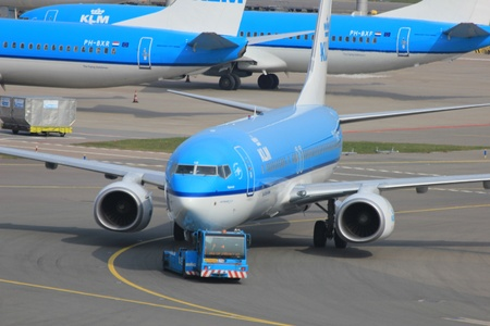 March, 24th, Amsterdam Schiphol Airport the Netherlands: a plane is being pushed back by a tug to avoid jet blast Stock Photo - 12878293