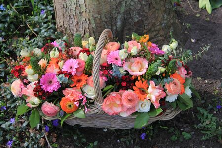 Wicker bsket with mixed flowers in bright colors photo