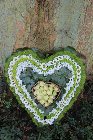 A sympathy flower arrangement near a tree in the shape on an heart photo