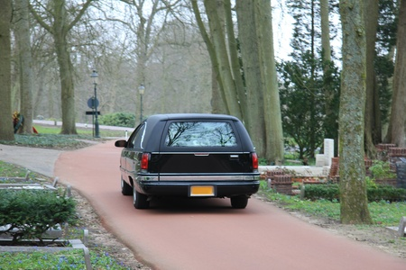A black hearse on a forest cemetery, driving slow