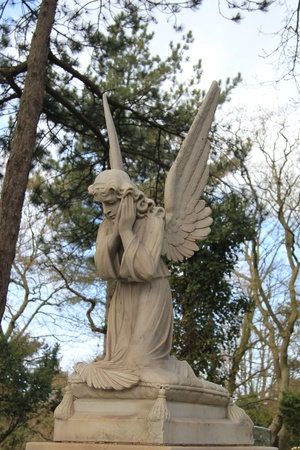A big angel guards over a grave on an ancient cemetery Stock Photo - 13198615