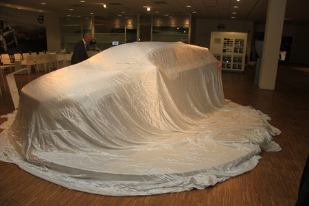 March 31st, Beesd the Netherlands Presentation of new Volvo V40, car covered with white sheet on display in showroom Stock Photo - 13337275
