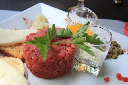 steak tartare: Steak tartare, populair French meal, served with condiments