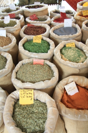 Various sorts of herbs and spices, displayed in bags on a french market photo