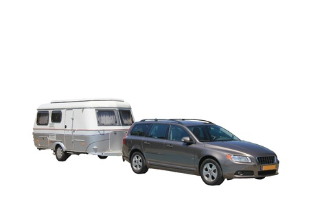 Middlesized car and caravan combination, ready to leave for vacation, isolated photo