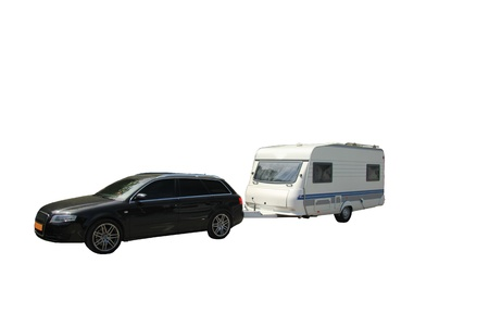 Middlesized car and caravan combination, ready to leave for vacation, isolated
