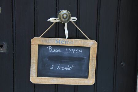 Small blackboard on a door with Lunch break message in French photo