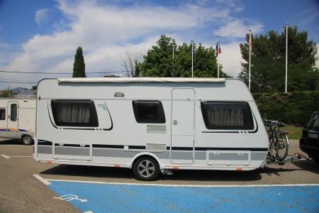 A middlesized caravan parked on a parking  photo