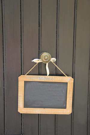 Small blackboard on a door, hanging on small rope photo