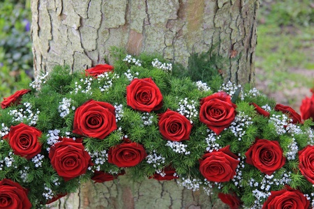 casket: Red roses and white gypsophila in a funeral wreath, detail near a tree