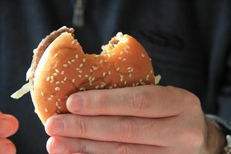 Man holding a hamburger on a bun photo