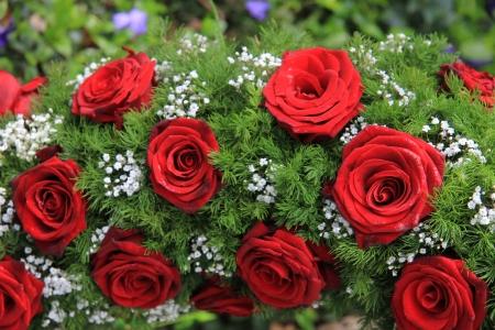 Piros rózsák és fehér fátyolvirág egy temetési koszorú