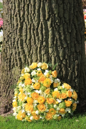 yellow roses and ranunculus in a heart shaped funeral arrangement photo
