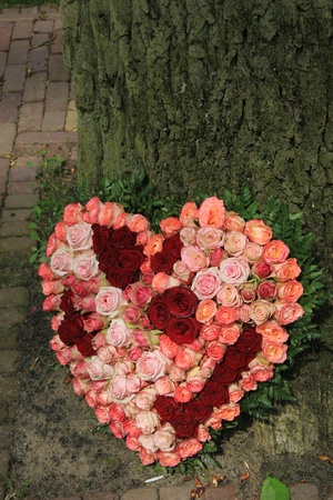 red and pink roses of different sizes in a heart shaped funeral arrangement photo
