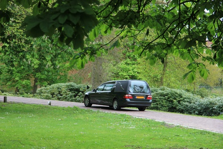 A black hearse on a forest cemetery, driving slow photo