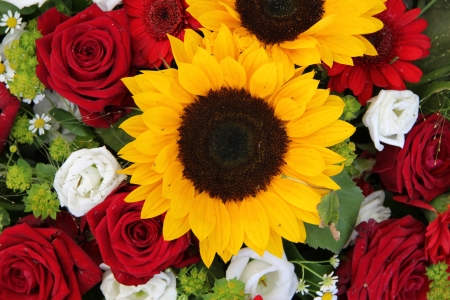 Bright yellow sunflowers and big red roses in a floral arrangement photo