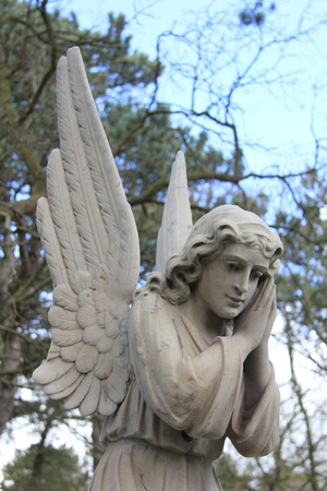 A big angel guards over a grave on an ancient cemetery Stock Photo - 14735255