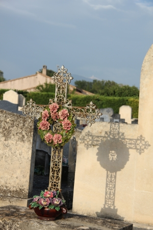 mortality: Cast iron cross ornament with ceramic sympathy wreath at an old cemetery in the provence Stock Photo