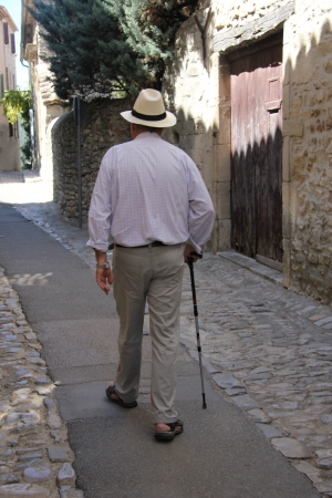 Older man walking in a Provencal street in France photo