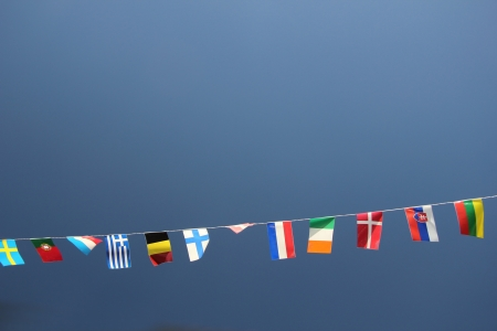 Flags of several european countries dancing in a clear blue sky photo