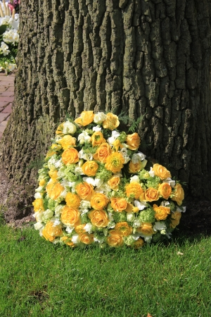 sympathy flowers: yellow roses and ranunculus in a heart shaped funeral arrangement