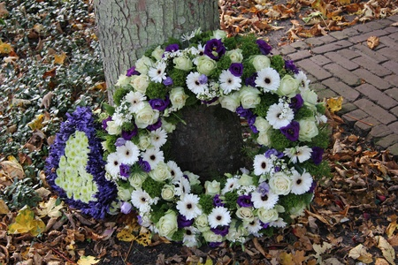 White and purple sympathy flowers in a funeral wreath