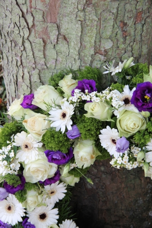 purple wreath: White and purple sympathy flowers in a funeral wreathm detail Stock Photo
