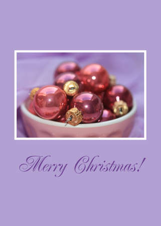 A bowl with pink christmas balls on a purple background photo