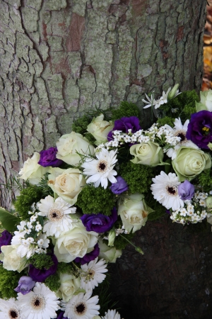 White and purple sympathy flowers in a funeral wreath, detail photo