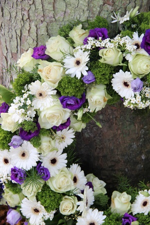 White and purple sympathy flowers in a funeral wreath, detail