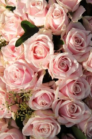 露を帯びた淡いピンクのバラの結婚式のセンター ピースの低下します。