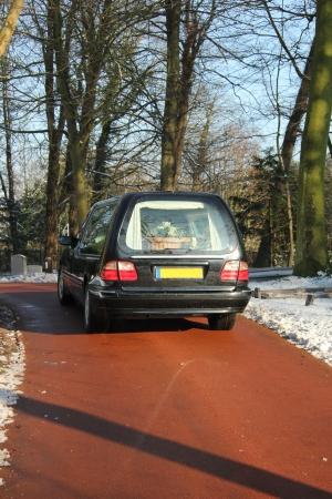 hearse: Black hearse on a winter cemetery Stock Photo