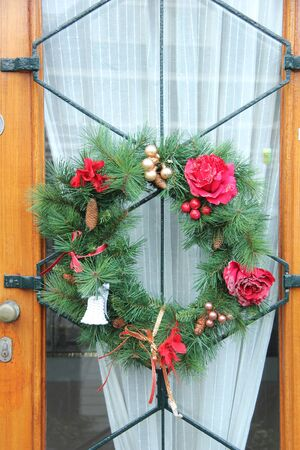 Christmas wreath with red roses on a glass door photo