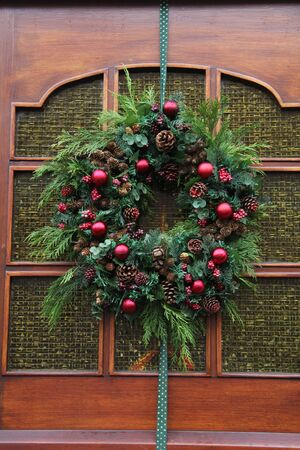 Christmas wreath on a glass door, decorated with red ornaments Stock Photo